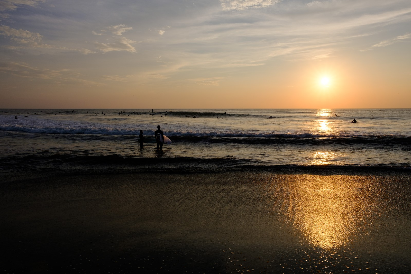 「朝日に照らされる引波の波打ち際とサーファー達(千葉県一宮町)」の写真