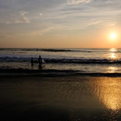 朝日に照らされる引波の波打ち際とサーファー達(千葉県一宮町)の写真