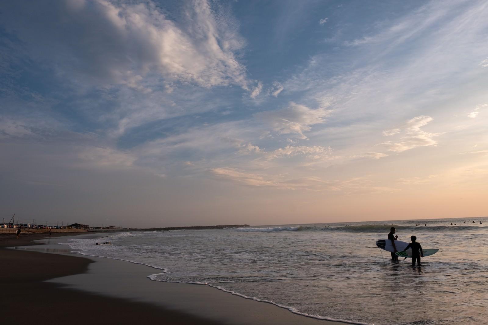 「一宮海岸と夕焼けを背にしたサーファー達(千葉県一宮町)」の写真