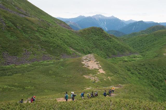 北アルプスの中央にある乗鞍新登山道と登山者の列の写真