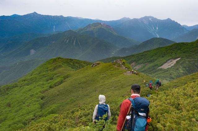 焼岳越しに笠ヶ岳を望む乗鞍新登山道と登山者の写真