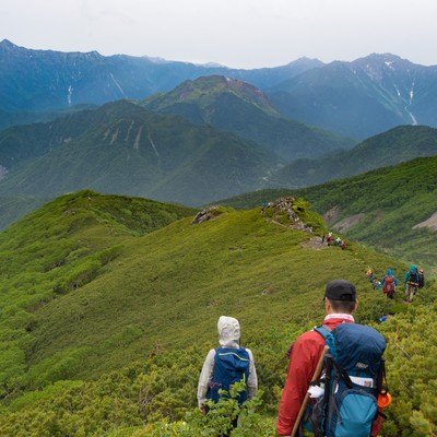 「焼岳越しに笠ヶ岳を望む乗鞍新登山道と登山者」の写真素材