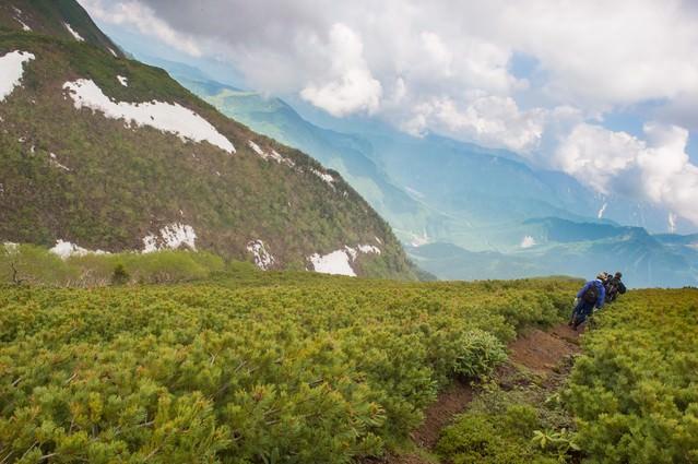稜線の気持ちいい風に吹かれて歩く地元民の写真