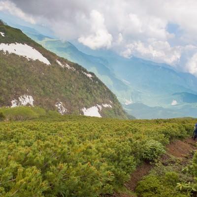「稜線の気持ちいい風に吹かれて歩く地元民」の写真素材