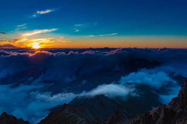 「槍ヶ岳山頂から見下ろす夕暮れの北アルプスの山々」のフリー写真素材