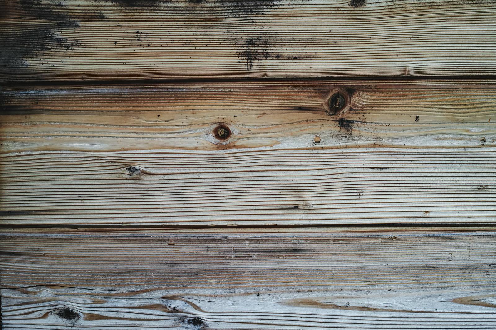 「黒いシミと木目の板(テクスチャ)」の写真