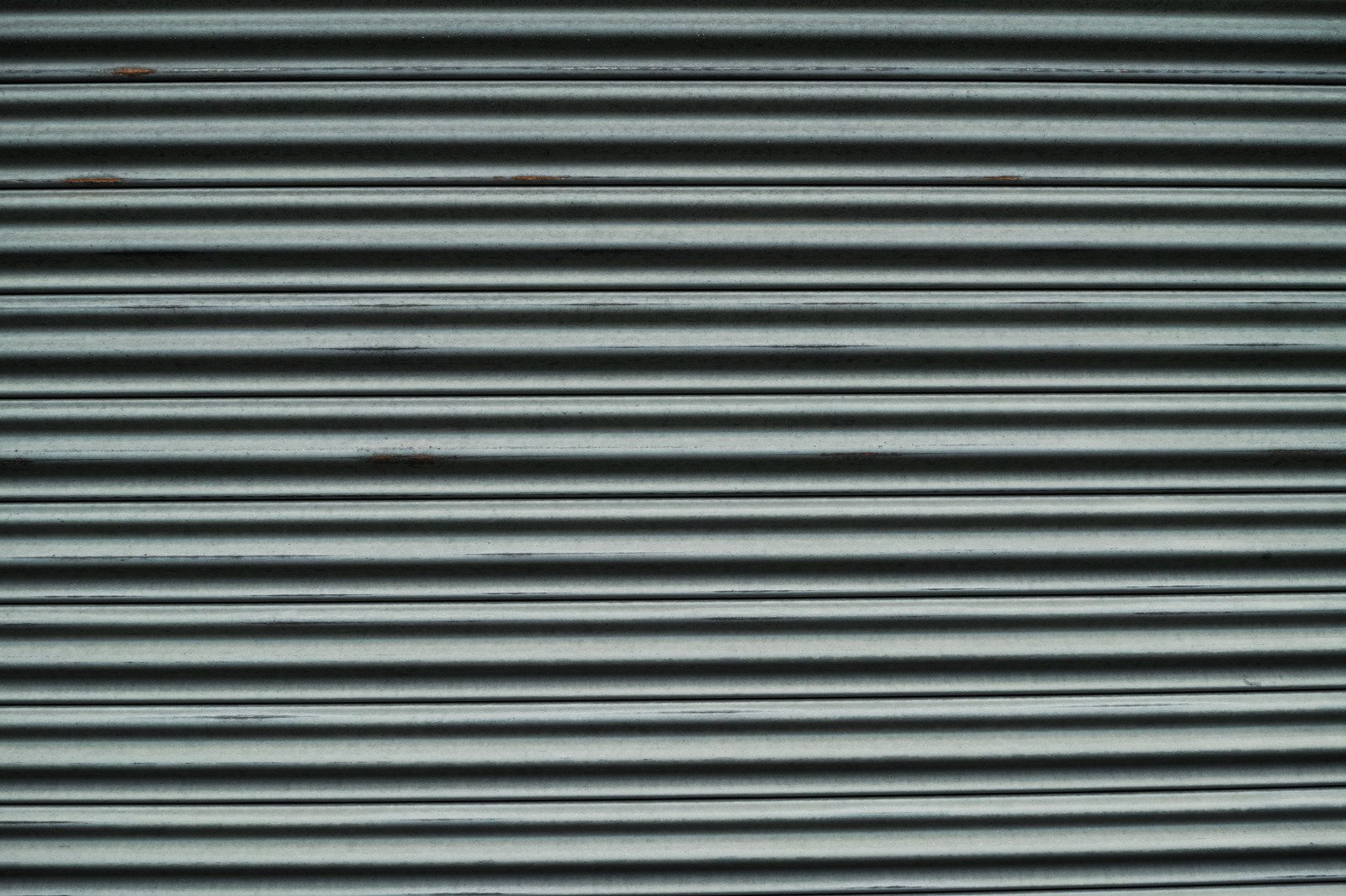 「擦れた部分に錆が浮き始める波板(テクスチャ)」の写真