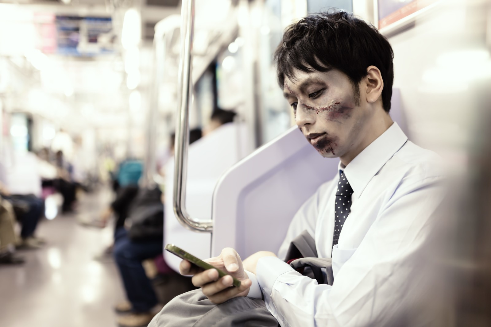 「電車通勤中に今日のパンデミックをチェックする意識高めの社畜ゾンビ」の写真[モデル:大川竜弥]