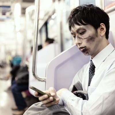 「電車通勤中に今日のパンデミックをチェックする意識高めの社畜ゾンビ」の写真素材