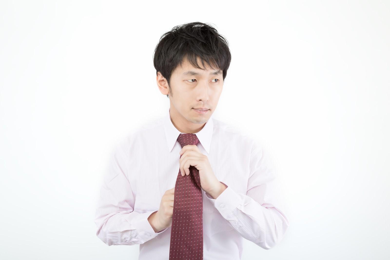 「ネクタイを締める広告代理店勤務の新入社員」の写真[モデル:大川竜弥]