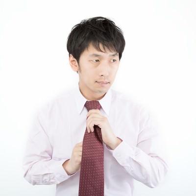 「ネクタイを締める広告代理店勤務の新入社員」の写真素材