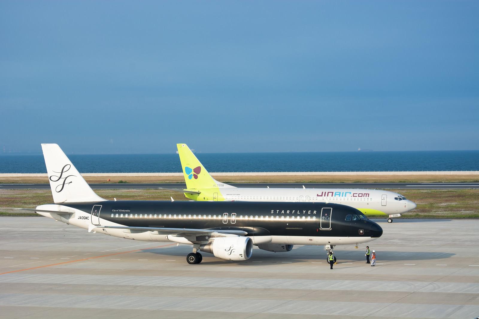 「最終チェックをする飛行機の横を通り駐機場に向かう着陸機」の写真