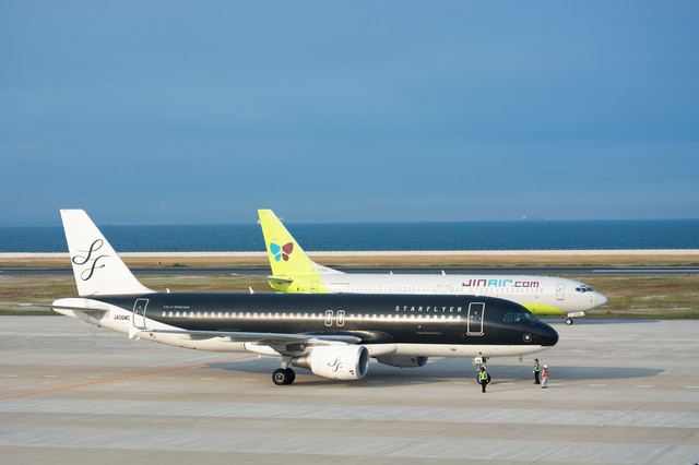 最終チェックをする飛行機の横を通り駐機場に向かう着陸機の写真