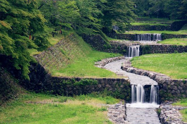 整備された小川の段差を流れ落ちる水の写真