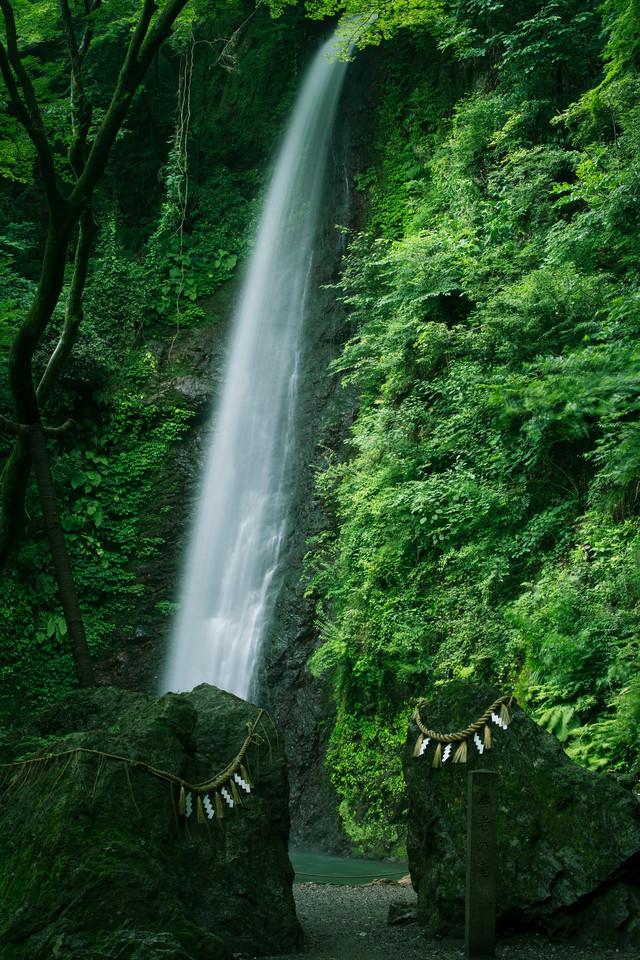 しめ縄の張られた岩と養老の滝の写真