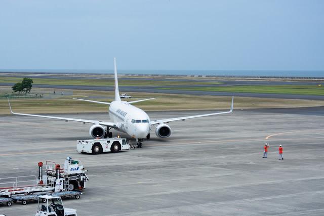 駐機場を離れプッシュバックされる飛行機と誘導するグランドハンドラー(山口宇部空港)の写真