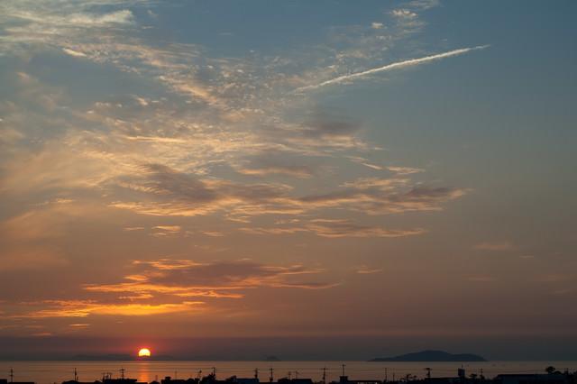 日没の太陽と海岸沿いの写真