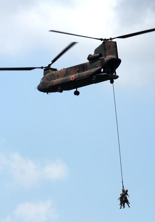 周囲を警戒しながら、CH-47に吊り下げられ撤収する隊員。の写真