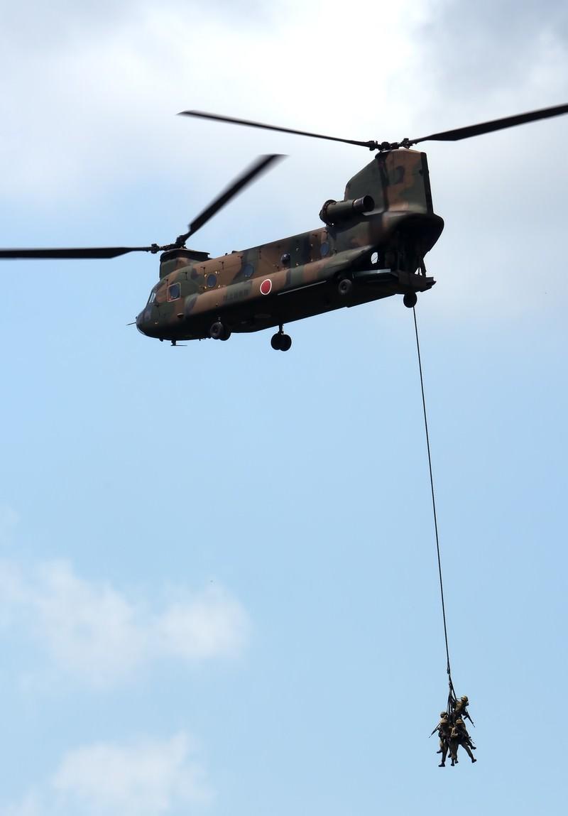「周囲を警戒しながら、CH-47に吊り下げられ撤収する隊員。」の写真