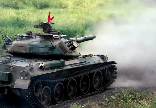 74式戦車と、発射直後に巻き上げられる土煙の写真