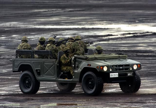 警戒しながら高機動車で移動する隊員たちの写真