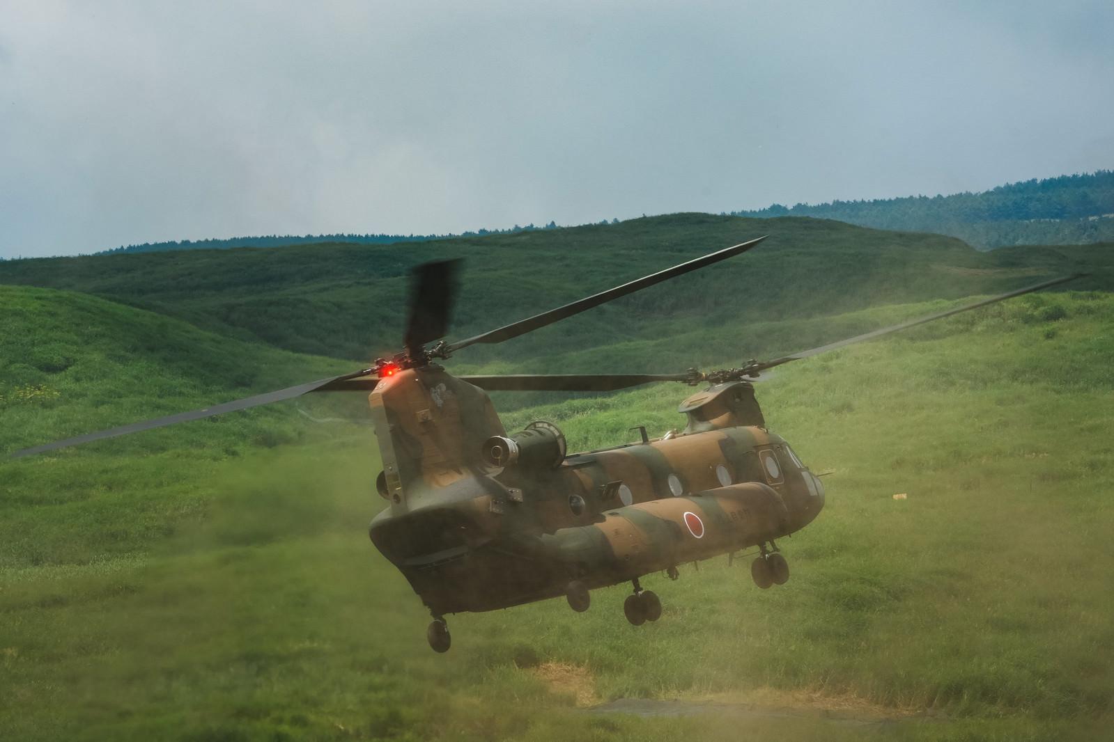 「自らのダウンウォッシュで巻き上げた砂埃の中着陸するチヌーク(CH-47)」の写真