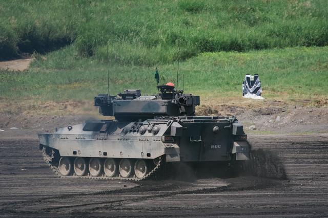 泥を蹴散らし進む89式装甲戦闘車の写真