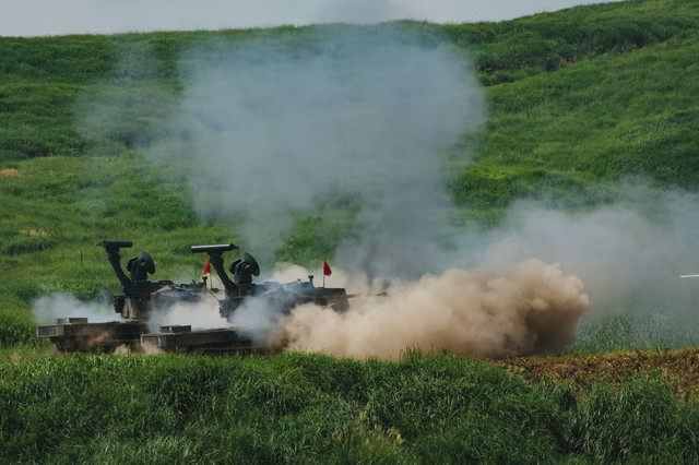 87式自走高射機関砲の射撃で巻き上がる砂埃の写真