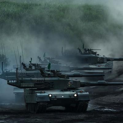 砲身を目標に向けたまま進む90式戦車の写真