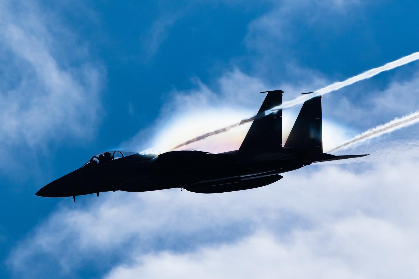 「虹を纏って進む戦闘機のシルエット(F-15)」の写真
