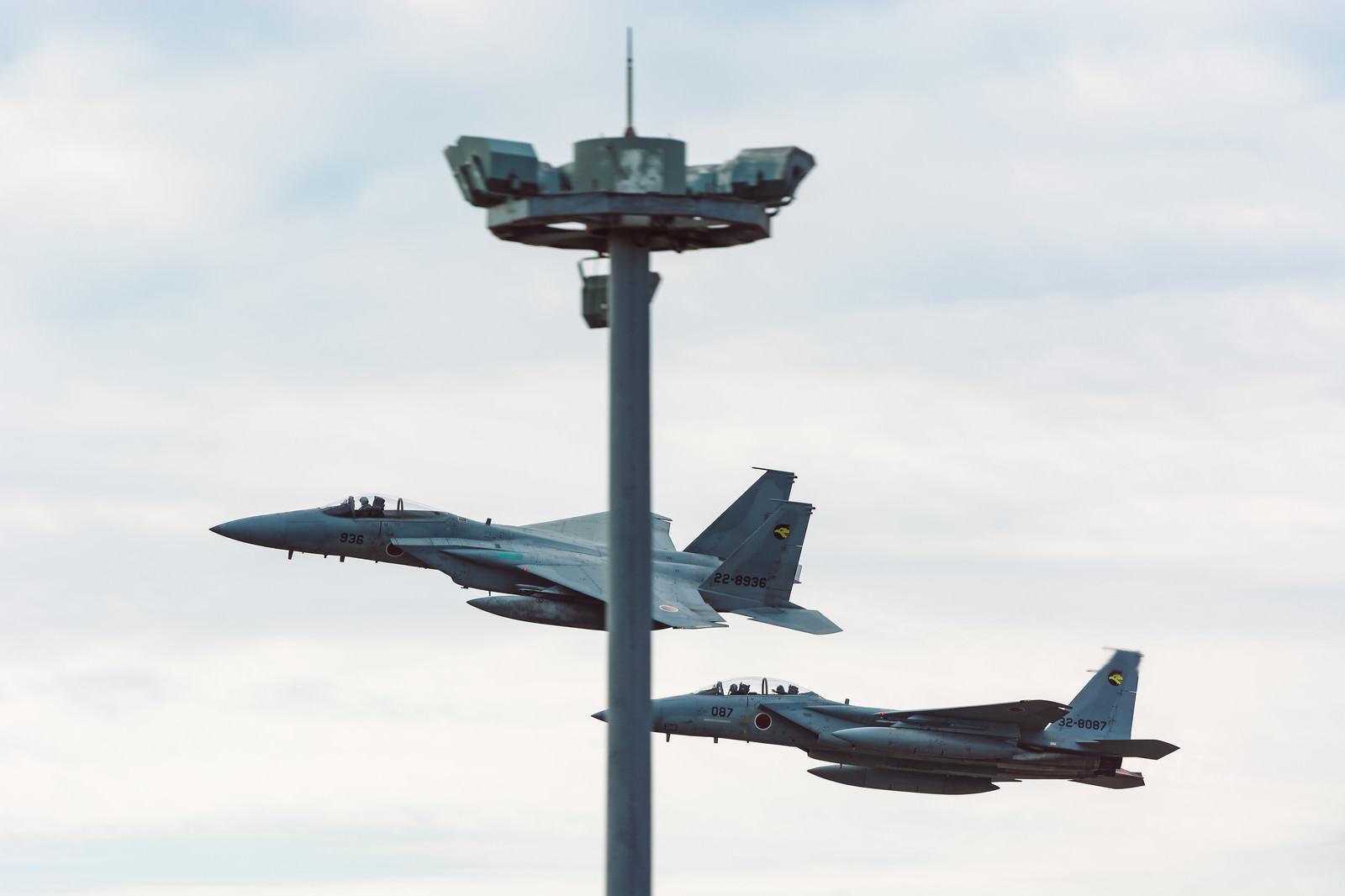 「鉄塔被りの併走する戦闘機(F-15)」の写真