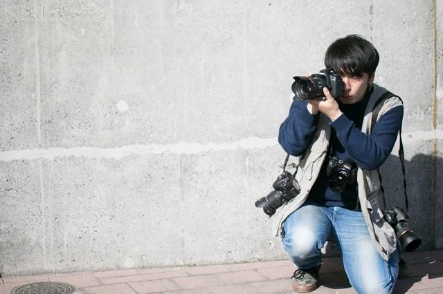 肩にカメラをかける機材過多の写真