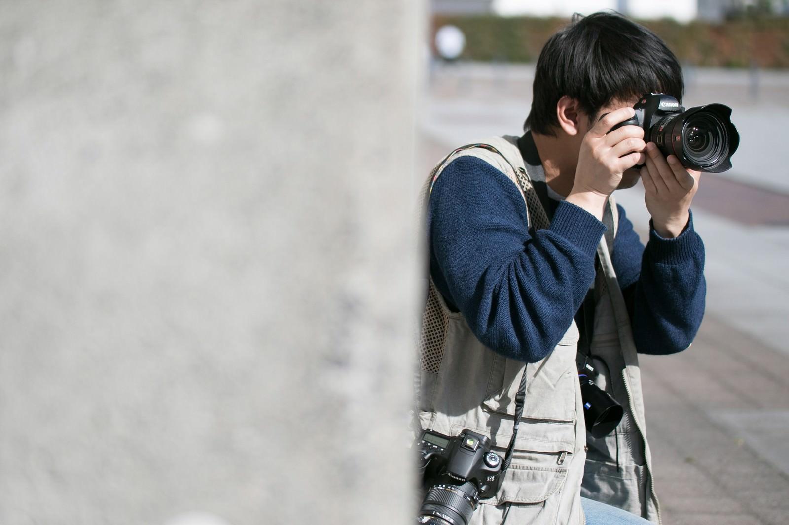 「ベストなポジションを探すカメラマン」の写真[モデル:大川竜弥]