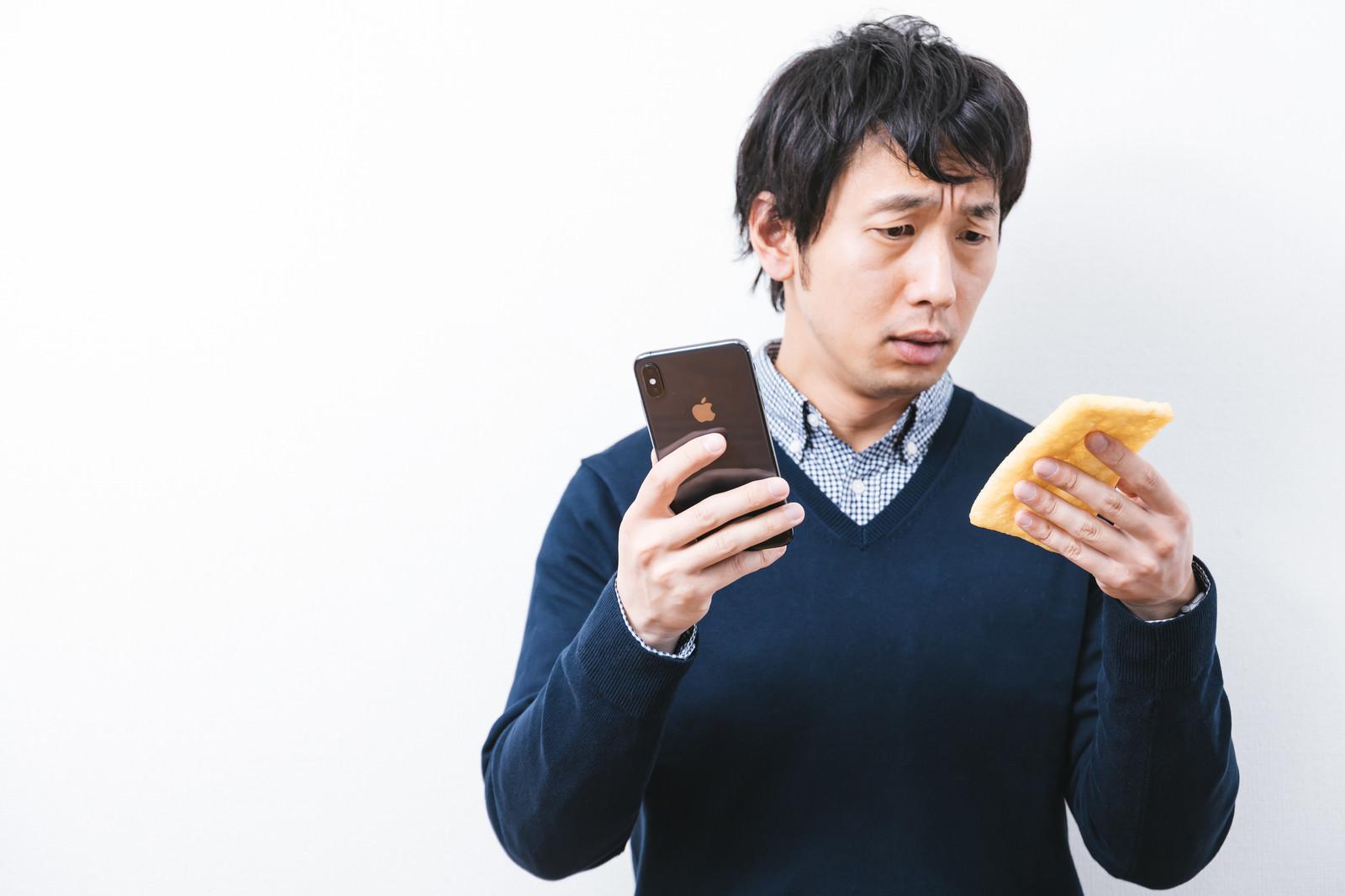 「iPhone XS Maxと油揚げの見分けがつかない男性」の写真[モデル:大川竜弥]