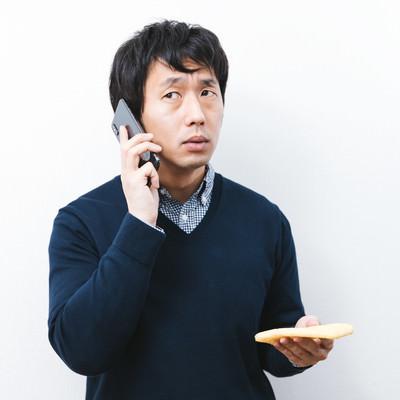 油揚げを愛でながら通話する男性の写真