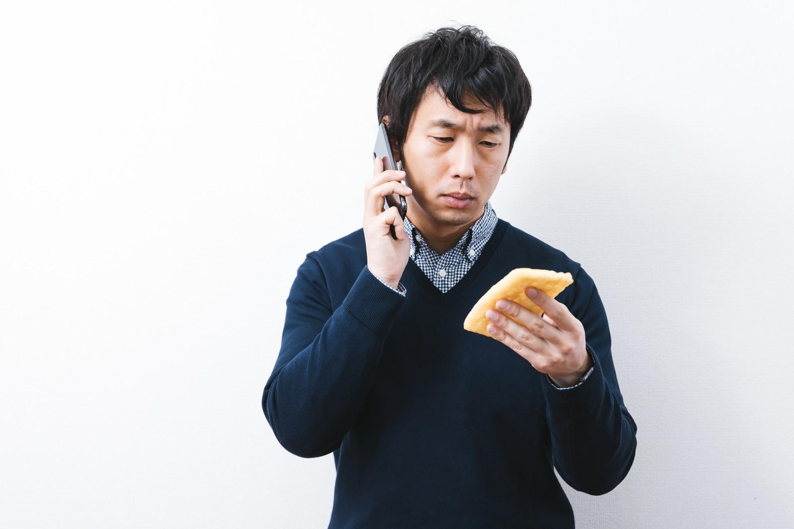 「油揚げに書かれたメモを見ながら通話する男性」の写真[モデル:大川竜弥]