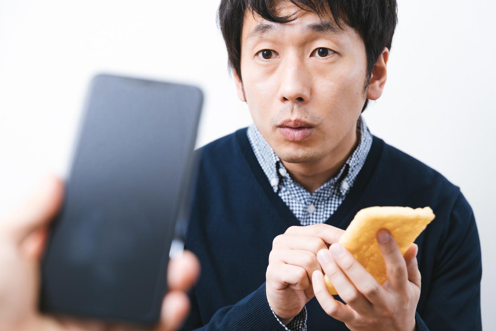 「iPhoneと油揚げでAirDropを試す男性」の写真[モデル:大川竜弥]