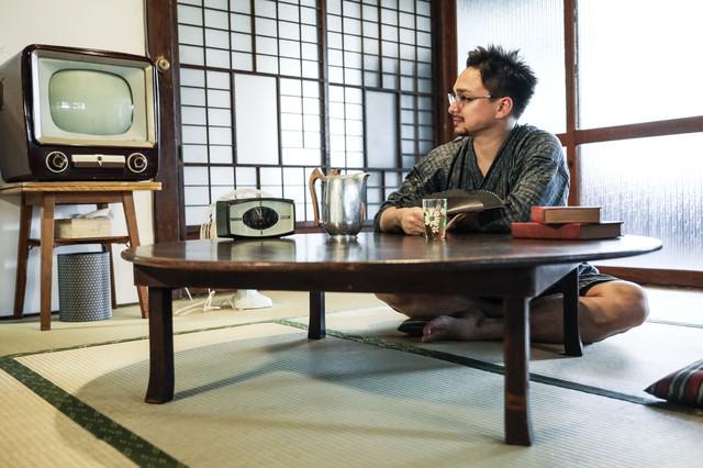 アナログテレビがある和室で甚平を着てくつろぐ外国人観光客の写真