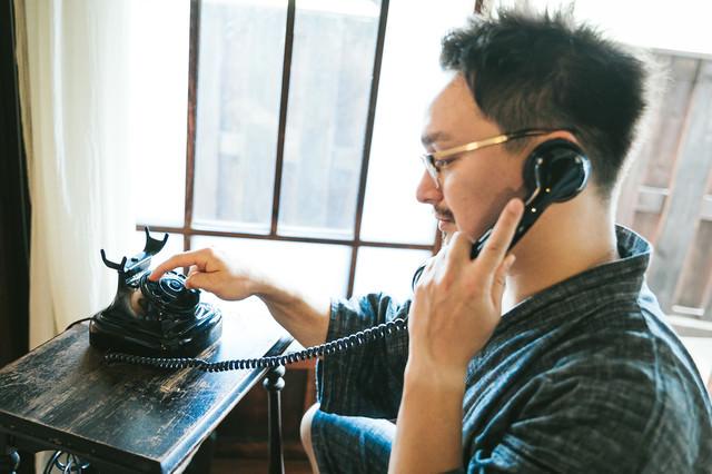 ダイヤル式電話機を使って電話をかけるドイツ人ハーフの写真