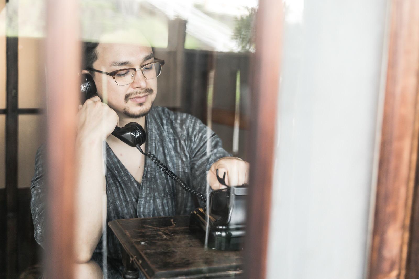 「黒電話を使って電話をかける外国人」の写真[モデル:Max_Ezaki]