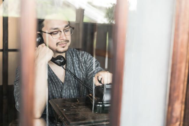 黒電話を使って電話をかける外国人の写真