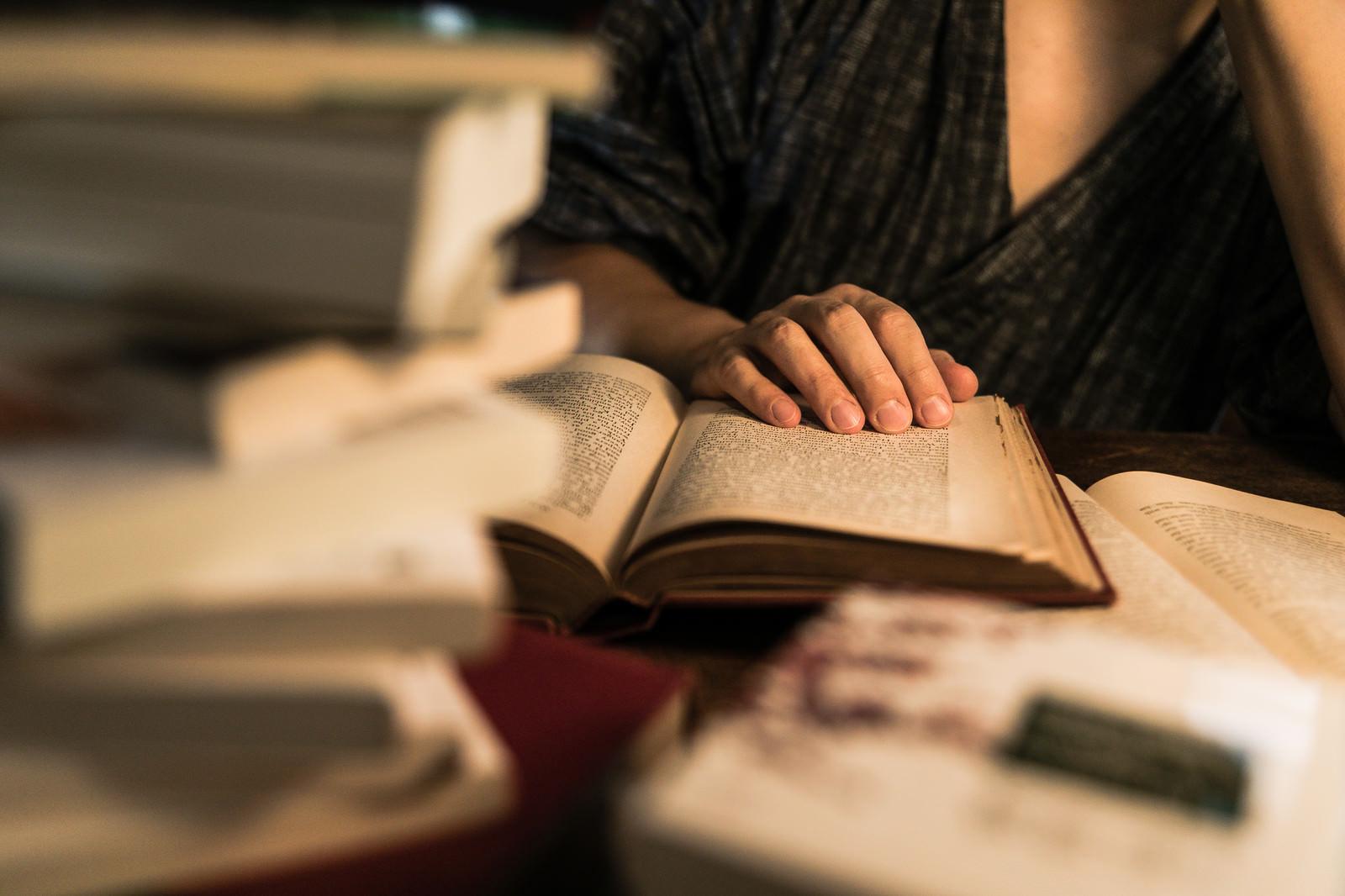 「積まれた本と、徹夜で調べものをする様子」の写真[モデル:Max_Ezaki]