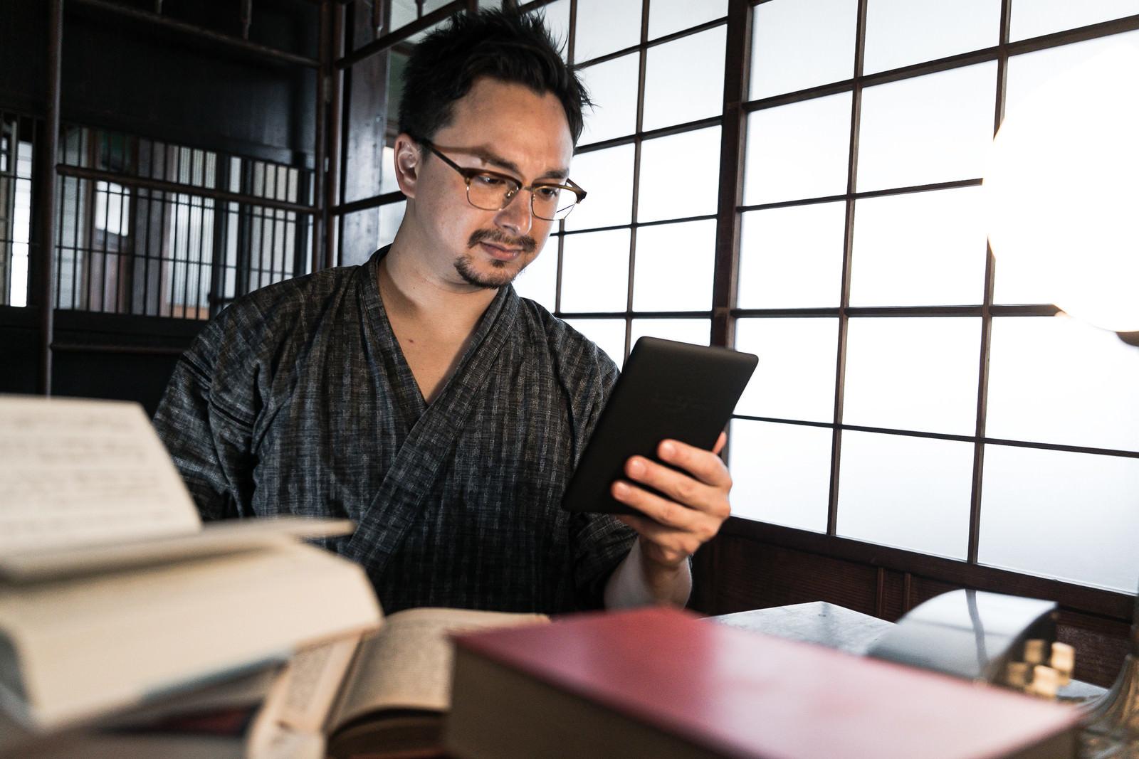 「積まれた本より電子書籍を読んでしまうデジタル世代」の写真[モデル:Max_Ezaki]