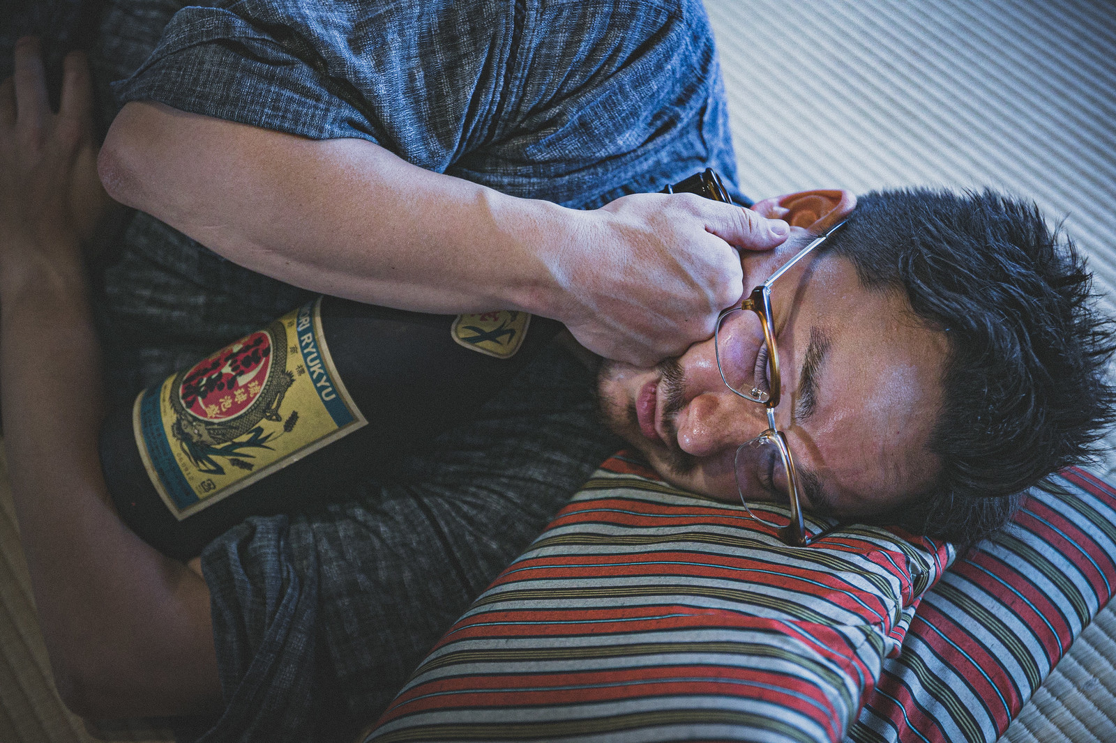 「日本酒の一升瓶を抱えて寝落ちする外国人」の写真[モデル:Max_Ezaki]