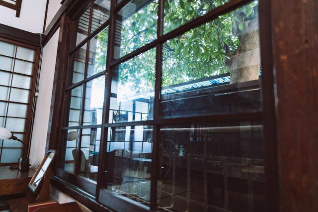 和室のガラス窓から見える庭の木漏れ日の写真