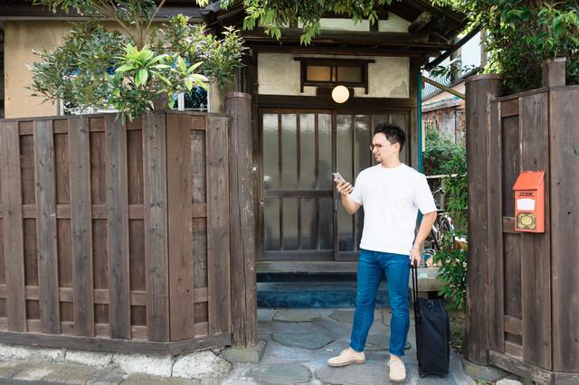古民家の軒先で予約を確認する外国人観光客の写真