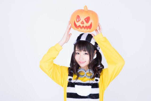 ハロウィンのかぼちゃお化けを持ち上げる仮装女子の写真