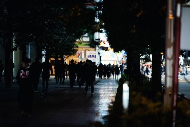 帰宅時間に駅へ歩く通行人達の写真