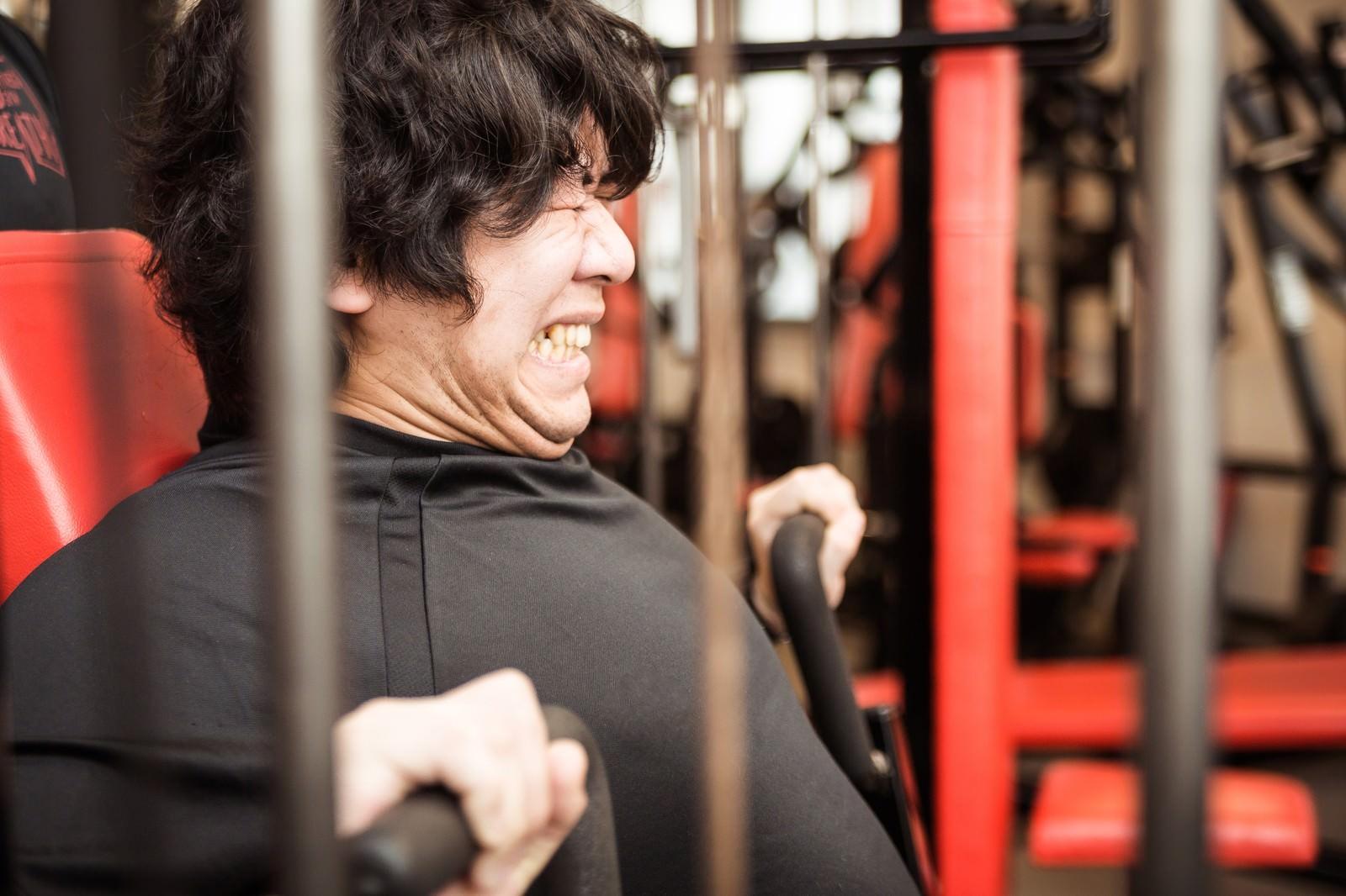 「チェストプレスで大胸筋を鍛えるトレーニー」の写真[モデル:朽木誠一郎]
