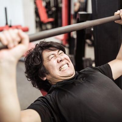 「インクラインベンチプレスで大胸筋上部を鍛えるトレーニー」の写真素材
